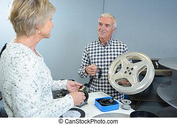 Senior couple preparing reels of cinema film