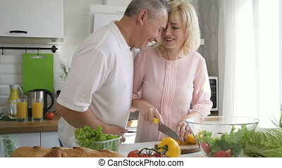 Senior couple preparing salad together in home kitchen.
