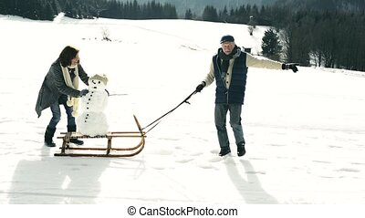 Senior couple pulling a snowman on a sledge in winter nature...