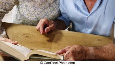 Senior couple reading a novel in cafe 4k
