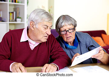 Senior couple reading bills at home - Elder couple looking ...