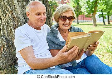 Senior Couple Reading in Park