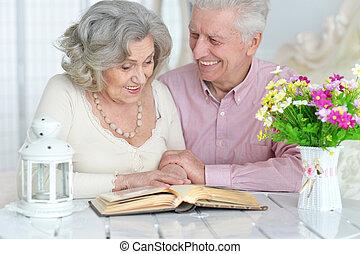 Senior couple reading magazine