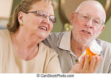 Curious Senior Couple Reading Prescription Medicine Bottle Together.