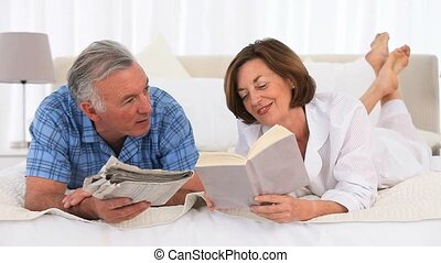 Senior couple reading on the bed