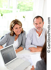 Senior couple ready to buy new house reading contract