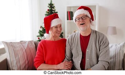 senior couple recording christmas video greeting -...