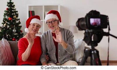 senior couple recording christmas video on camera -...