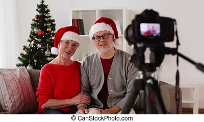 senior couple recording christmas video on camera -...