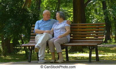 Senior couple relaxed talking on the park bench