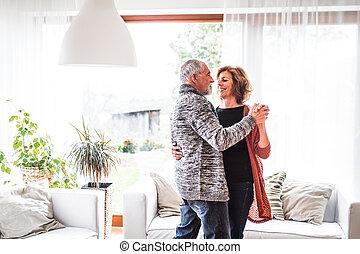 Senior couple relaxing at home, dancing.