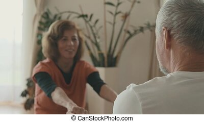 Senior couple relaxing at home, exercising. - Happy senior...
