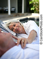 Senior couple relaxing by the pool