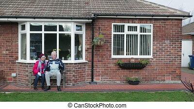 Senior Couple Relaxing in the Garden - Senior couple are...