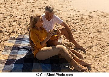 Senior couple reviewing through photos on mobile phone at beach