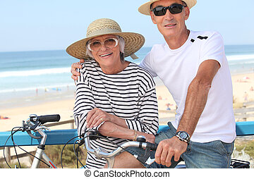 Senior couple riding bikes by the ocean
