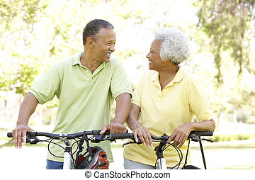 Senior Couple Riding Bikes In Park