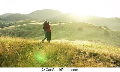 Senior couple runners hugging on meadow outdoors at sunrise...