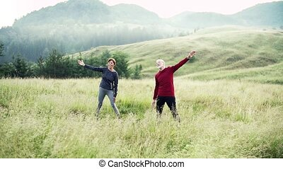 Senior couple runners stretching on meadow outdoor in foggy...