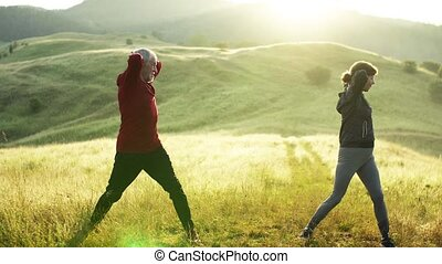 Senior couple runners stretching on meadow outdoor in nature...