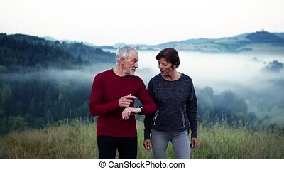 Senior couple runners walking on grassland outdoor in foggy...