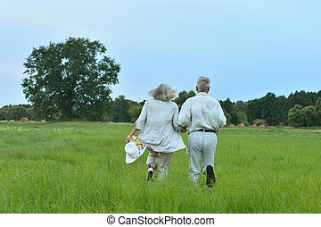 Senior couple running in field
