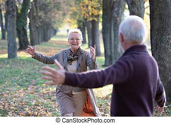 Senior couple running in hug