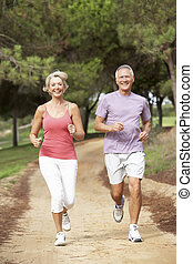 Senior couple running in park