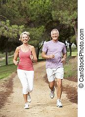 Senior couple running in park