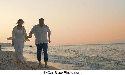 Senior couple running on the beach at sunset