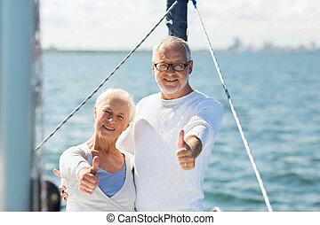 sailing, age, tourism, travel and people concept - happy senior couple hugging on sail boat or yacht deck floating and showing thumbs up in sea