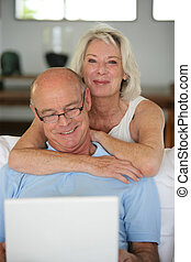 Senior couple sat with laptop computer