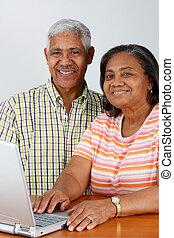 Senior Couple - Senior Minority Couple Working On A Computer