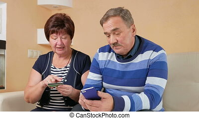 Senior couple shopping in internet shop by credit card and phone. Man and woman sitting at home data card are administered carefully on the couch