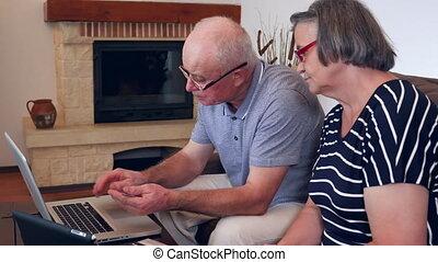 Senior couple shopping online using credit card on laptop