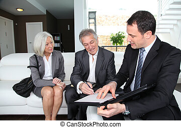 Senior couple signing financial contract for property...