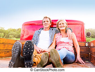 Senior couple sitting in back of red pickup truck