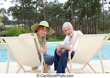 Senior couple sitting in deckchairs by a pool