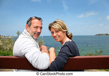 Senior couple sitting in front of beautiful sea view
