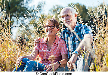 Senior couple sitting in the grass enjoying themselves