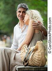 senior couple sitting on a bench
