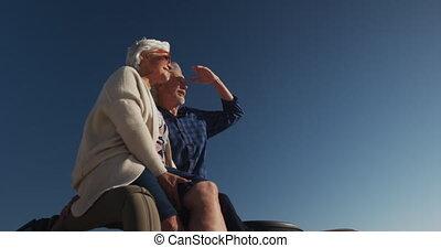 Senior couple sitting on a car