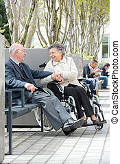 senior couple sitting on a park bench and holding hands