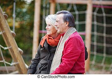 Senior couple sitting on a playground