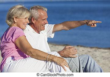 Senior Couple Sitting on Beach Pointing