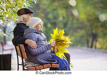Senior couple sitting on bench in park