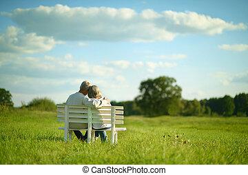 senior couple sitting on bench - Amusing senior couple...