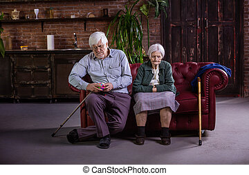 Senior couple sitting on couch. Couple in quarrel, not talking to each other.
