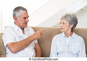 Senior couple sitting on couch having an argument