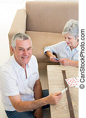 Senior couple sitting on floor playing cards